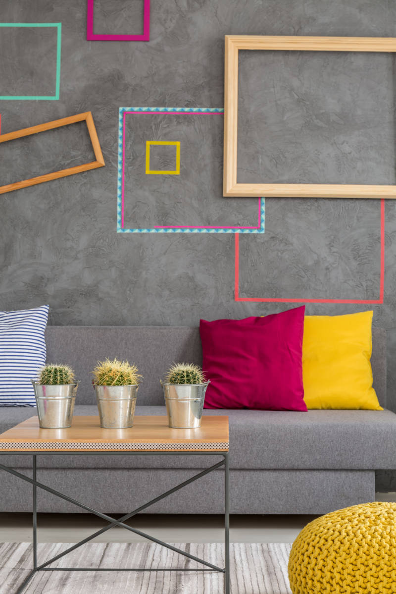 Modern design of grey lounge with colorful pillows and frames on the wall